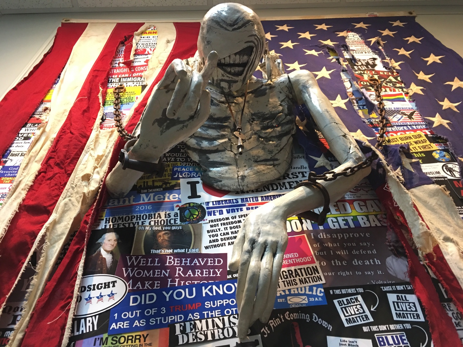 Torso, arms and hands of a chained body attached to a vertical wall with a tattered flag over various political prints