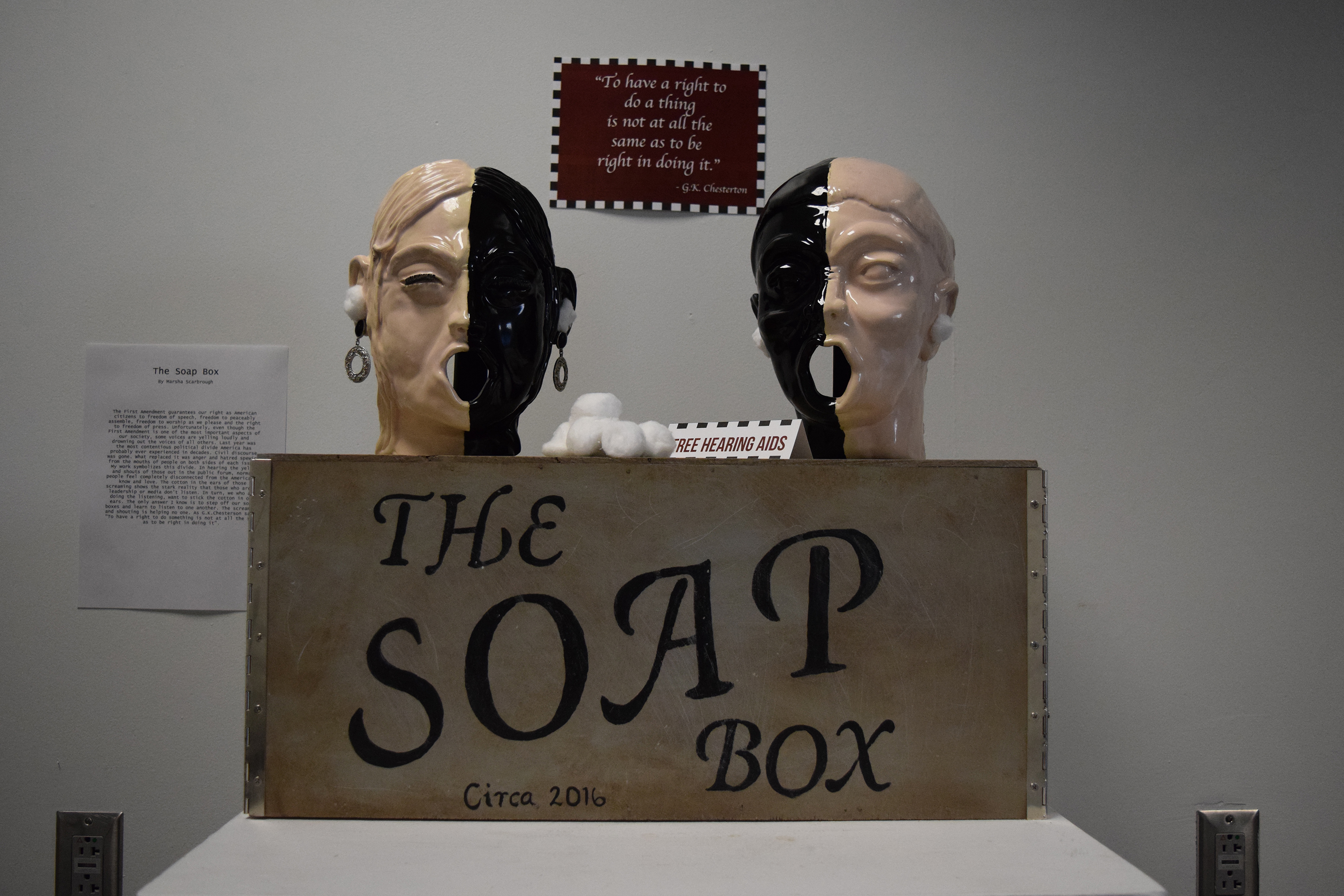 "Box with ""The Soap Box"" written on the front side. On top of the box are two heads, each split with one side tan and the other black. Cotton balls are in the ears. One head has earrings."