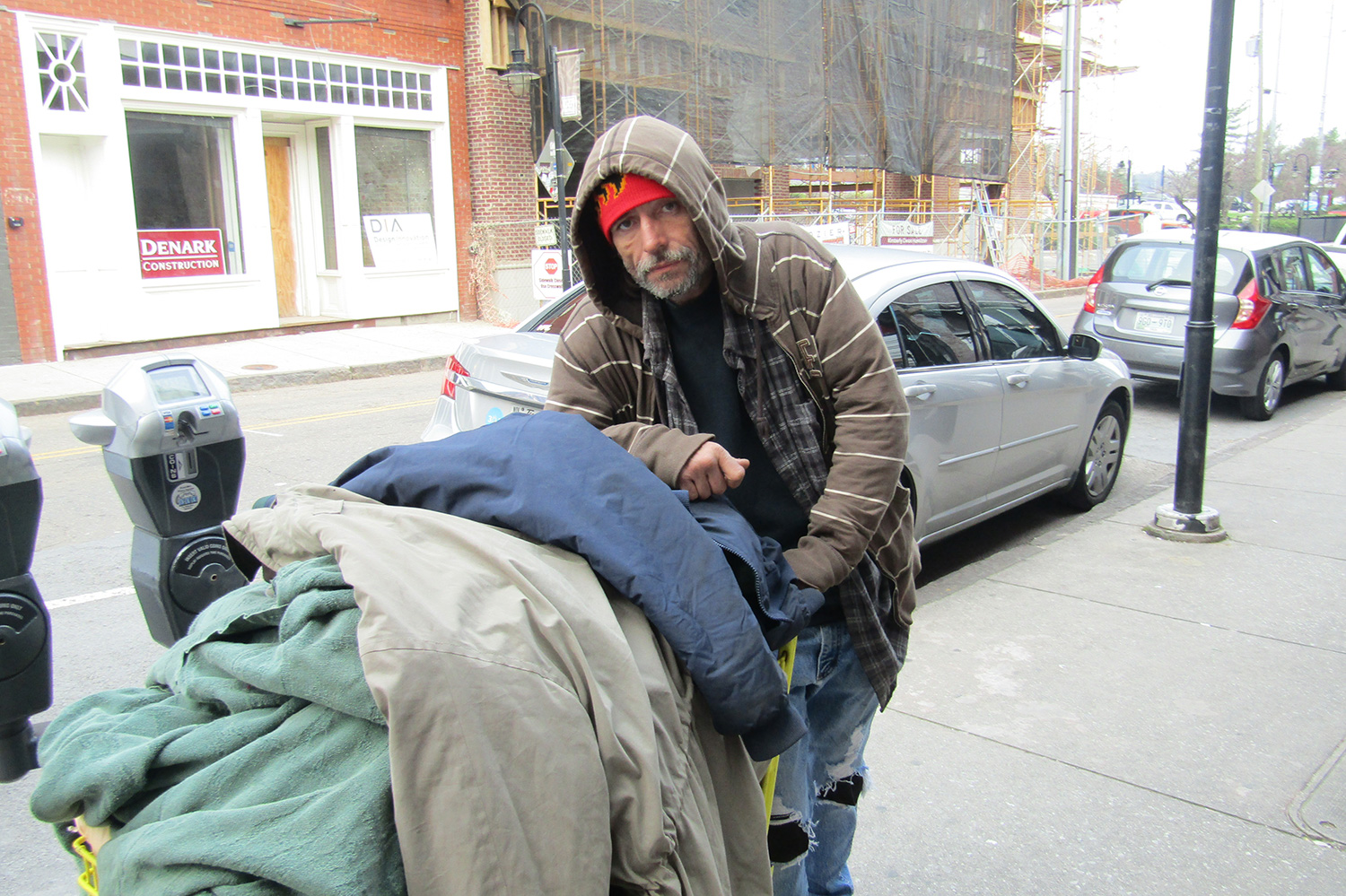 Photograph of a homeless man with a cart. The background is a city street with parked cars.