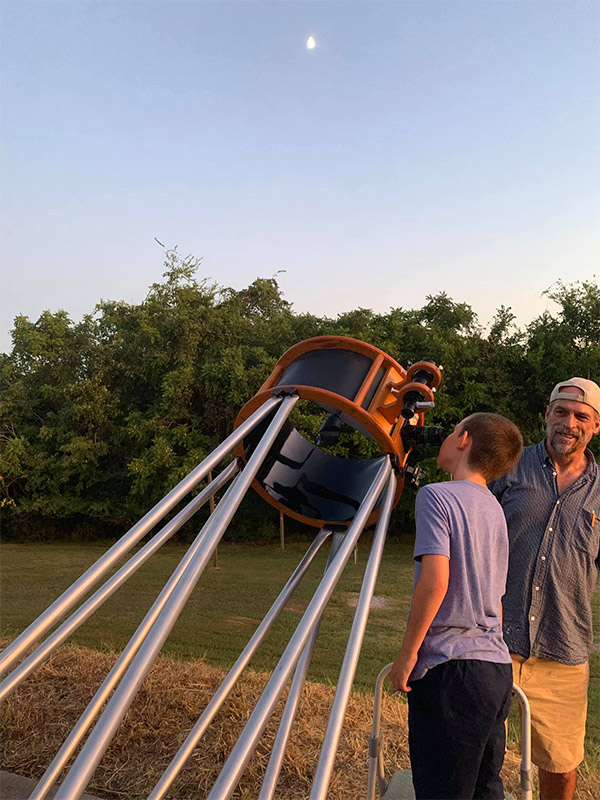 John Jaruzel, who donated the powerful telescope shown to Roane State's Tamke-Allan Observatory, helps a young visitor get acquainted with the device.