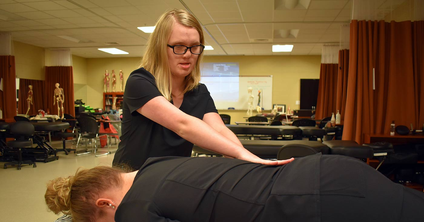 Blind since she was 6, Harley Sharpe practices massage on another of the students in a massage therapy class.