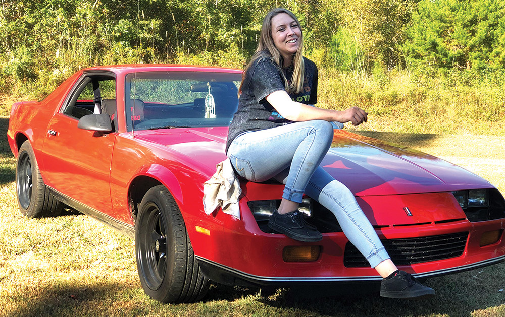 A smiling Briana Gaines sits atop her labor of love, a 1986 Chevrolet Camaro that the Roane State Community College student has been restoring for the past three years.