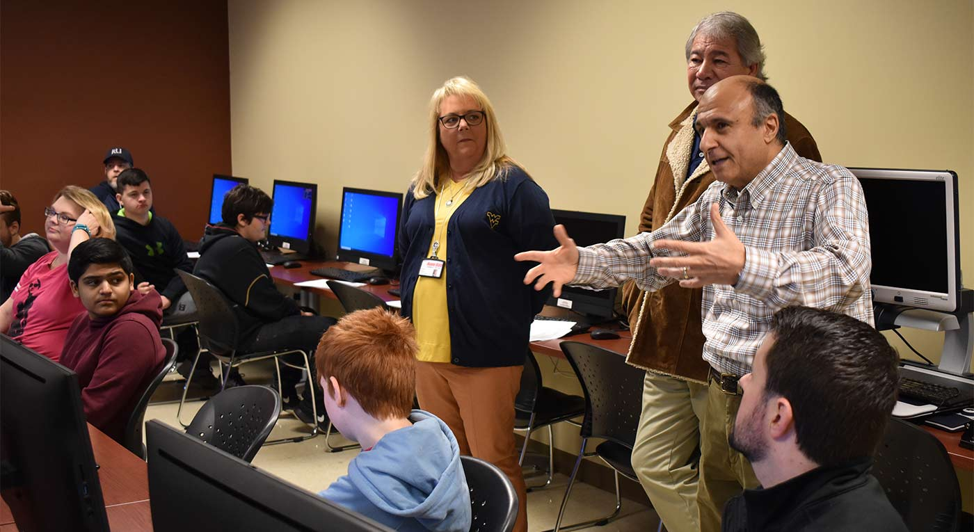 Dr. George Meghabghab, director of Roane State's Computer Information Technology program, gestures at the start of the college's second annual cybersecurity competition. Also pictured: Dr. Diane Ward, the college's vice president for student learning, and Bruce Cantrell, interim dean of mathematics and sciences.