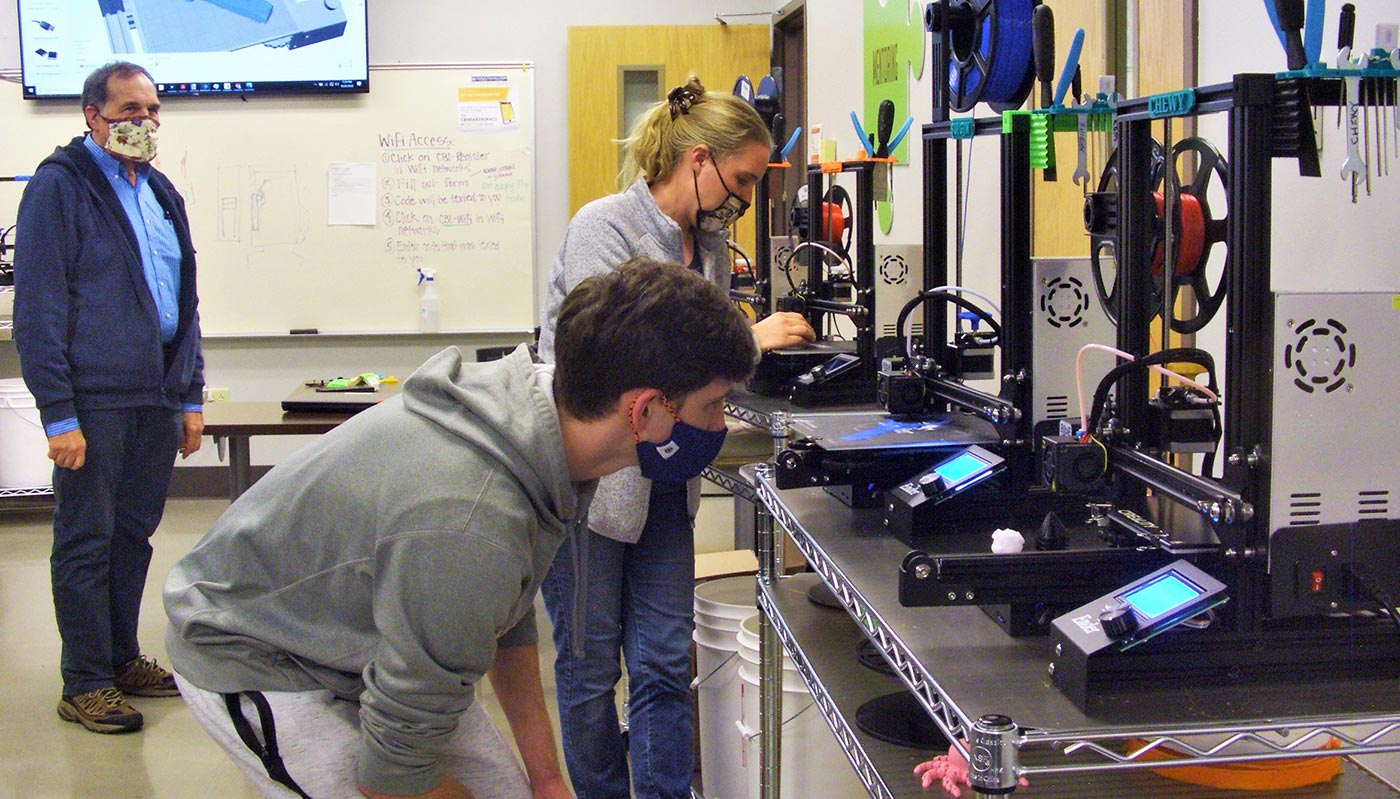 Tom McDunn watches as Roane State students Josh Palmer and Janel Hostetler use 3D printers.