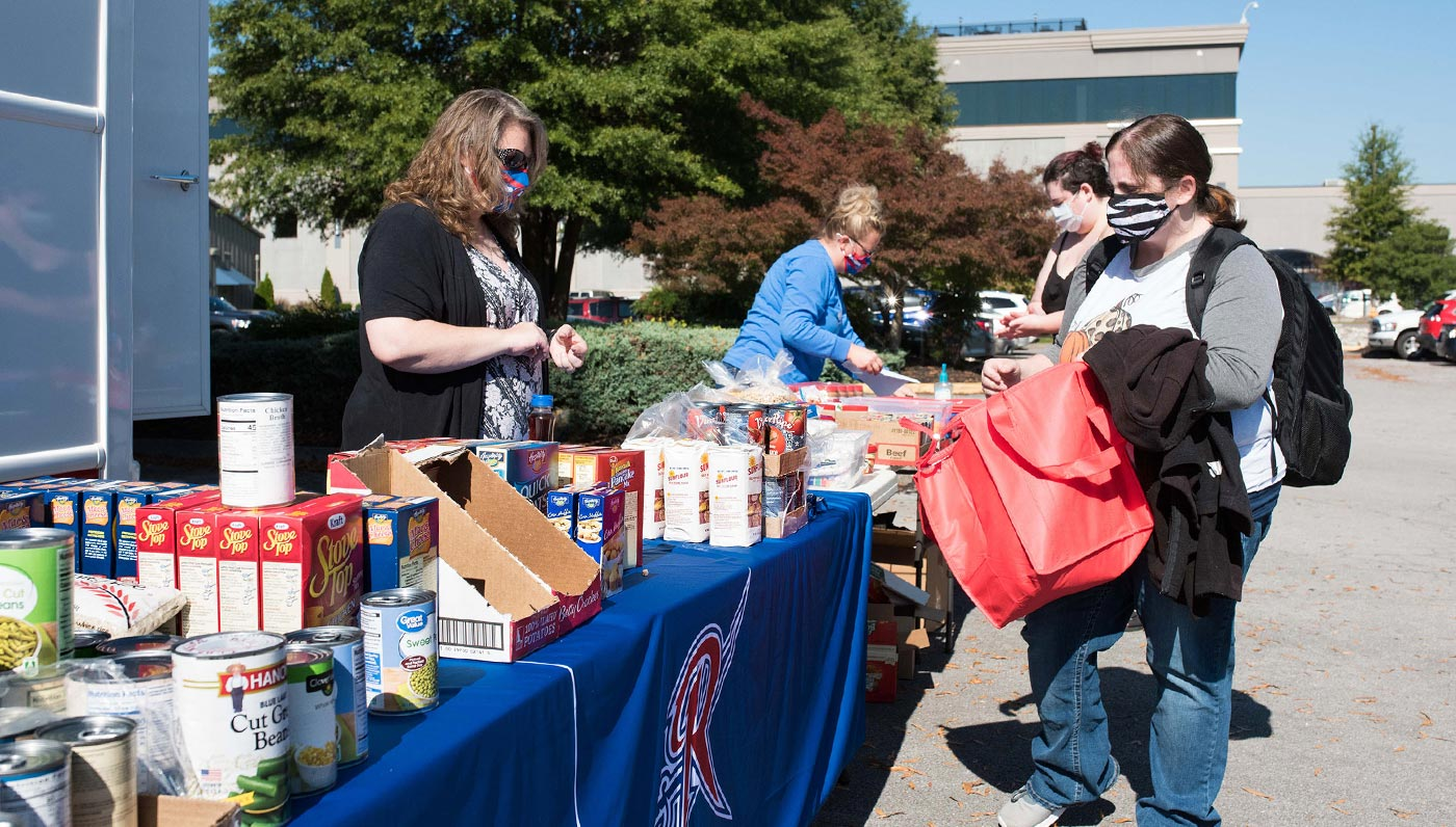 Students and staff with tables of food pantry items