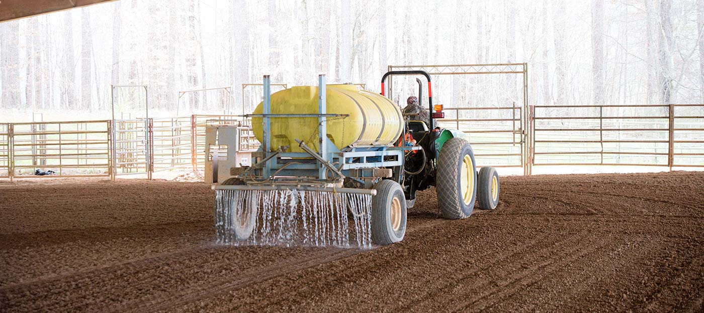 Tractor spreading liquid on dirt.